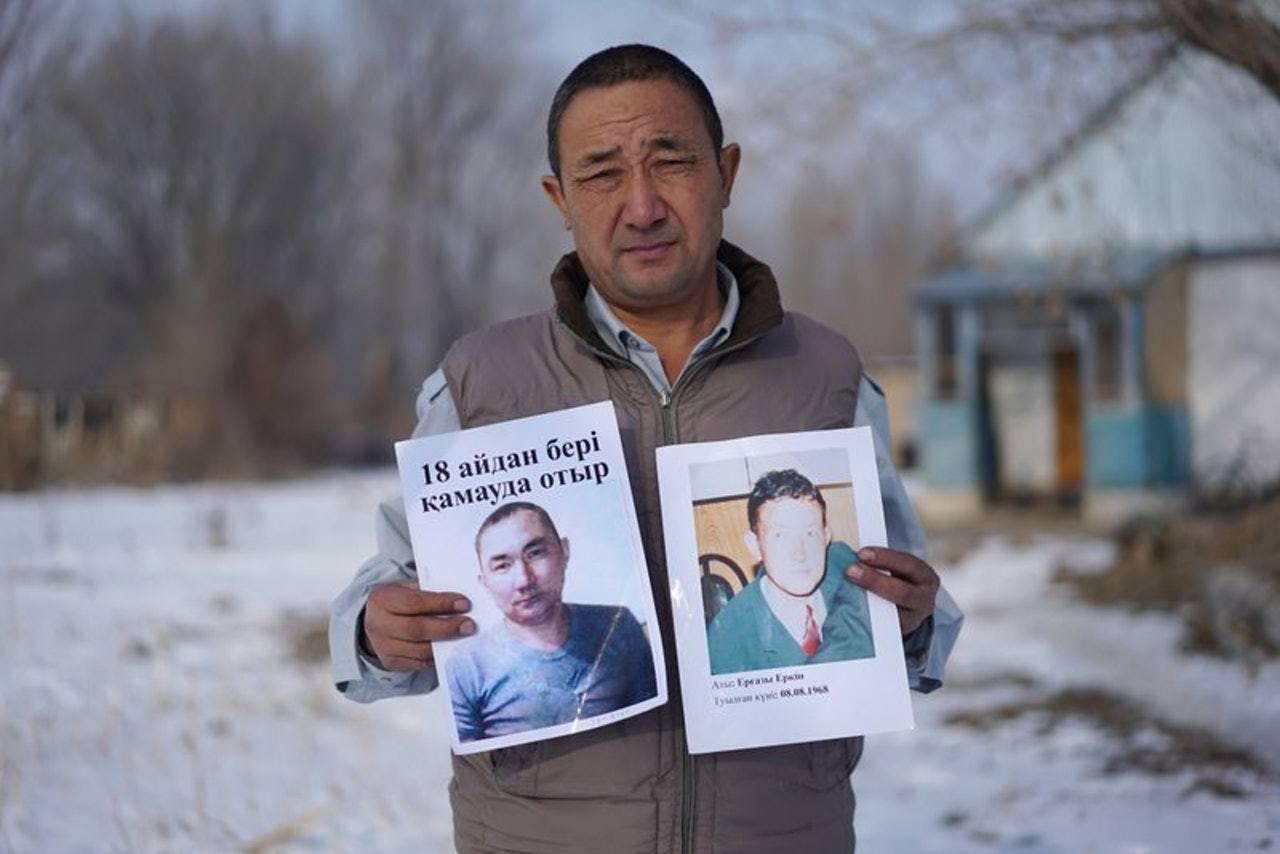 一名哈薩克男子展示他在中國境內被拘的親人的照片。(美聯社)