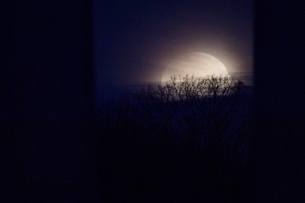 2018年1月31日在華府國會大廈柱後面看到月亮。這個滿月是「獨一無二」,它是一...