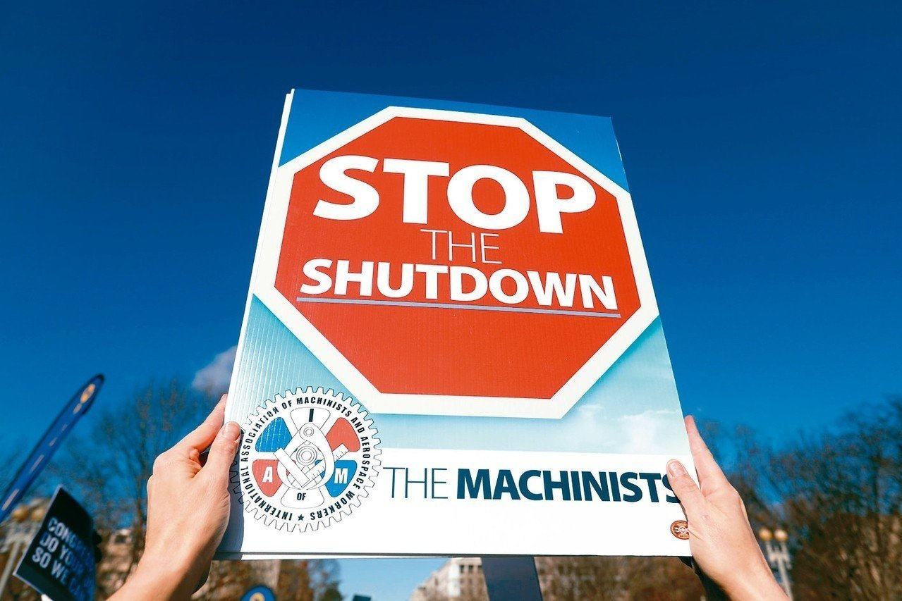 一名抗議者在白宮外高舉「停止關閉(政府)」標語。 路透