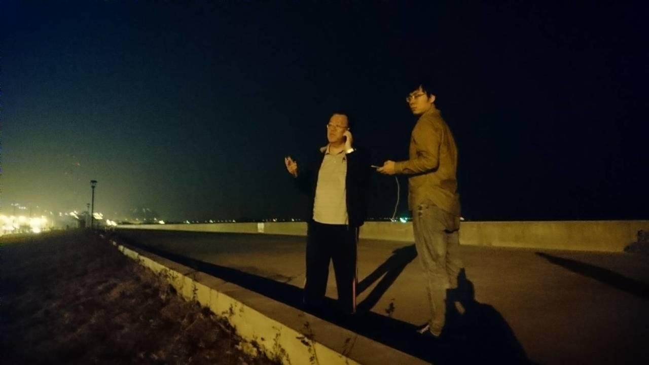 高雄市環保局長袁中新(左)夜宿茄萣,遠方就是興達電廠。圖/高雄市環保局提供