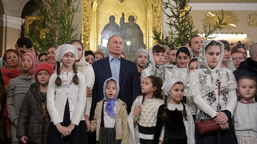 普亭(中)日前在聖彼得堡東正教教堂內跟民眾慶祝耶誕節。 (路透)