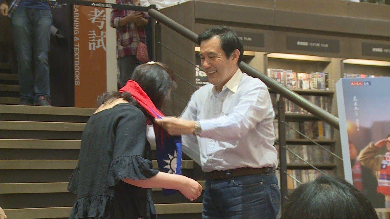 前總統馬英九出席高雄簽書會,幫粉絲圍圍巾,針對過去八年執政有支持與批評,他深感自...