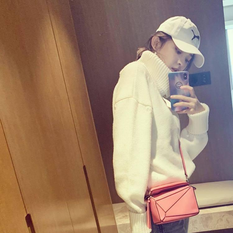 古力娜扎以白色高領衫配襯粉紅色Puzzle手袋。圖/取自IG