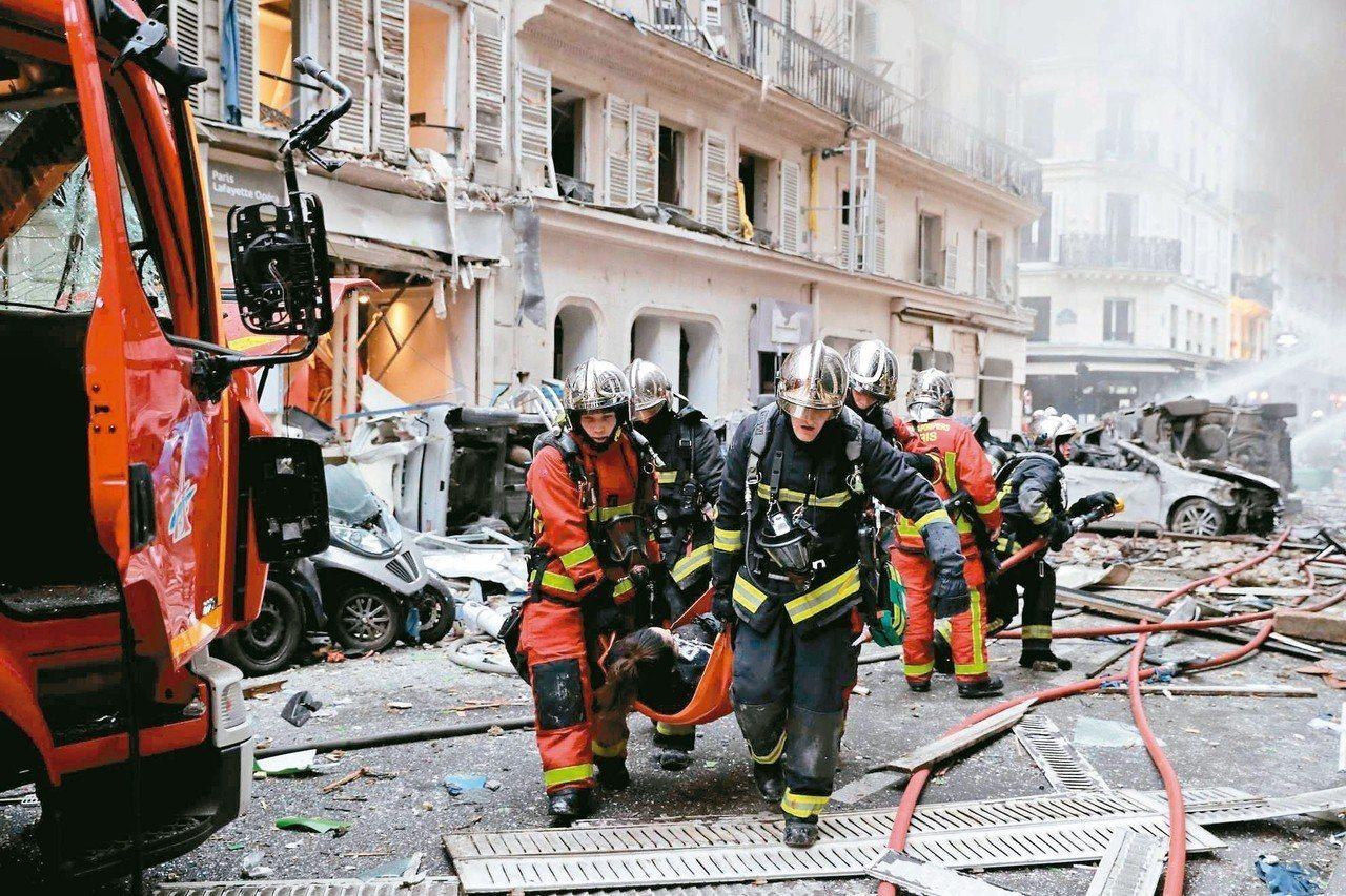 法國巴黎市中心十二日驚傳爆炸,約兩百多名警消在現場協助撤出傷患。 (法新社)