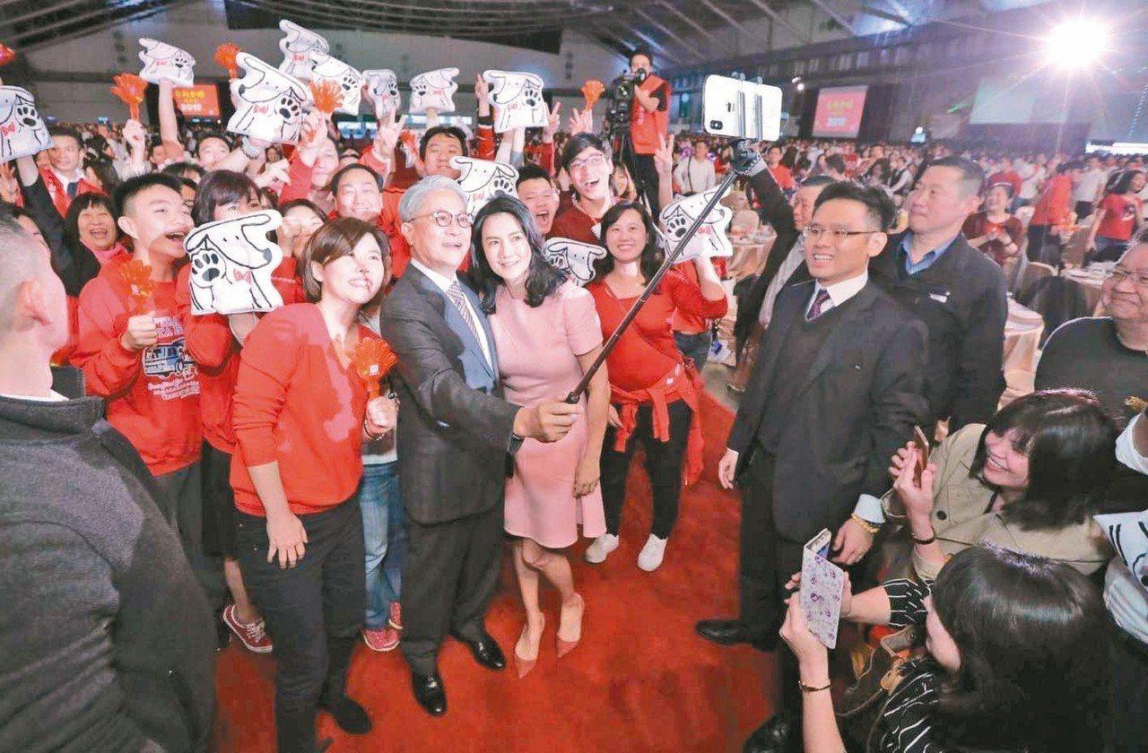 台新金舉辦旺年會,董事長吳東亮(中)及夫人彭雪芬在員工簇擁下進場,開心之餘玩起自...