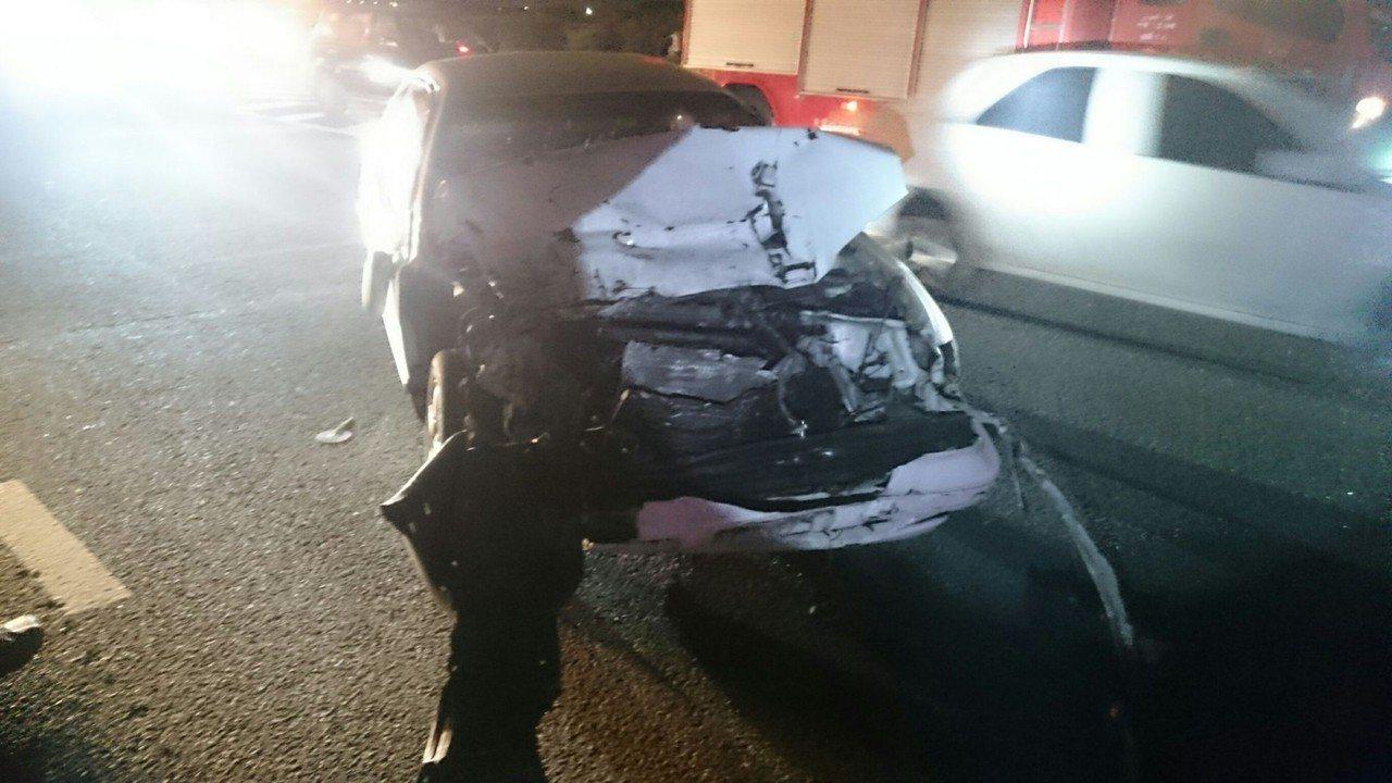 撞擊力道太大,白色自小客車車頭全毀。 記者卜敏正/翻攝