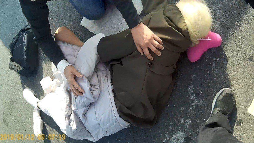 一名駕車經過的男子憂心倒臥路中央的老婦人受二度傷害,以轎車車身做警示,擋在事故現...