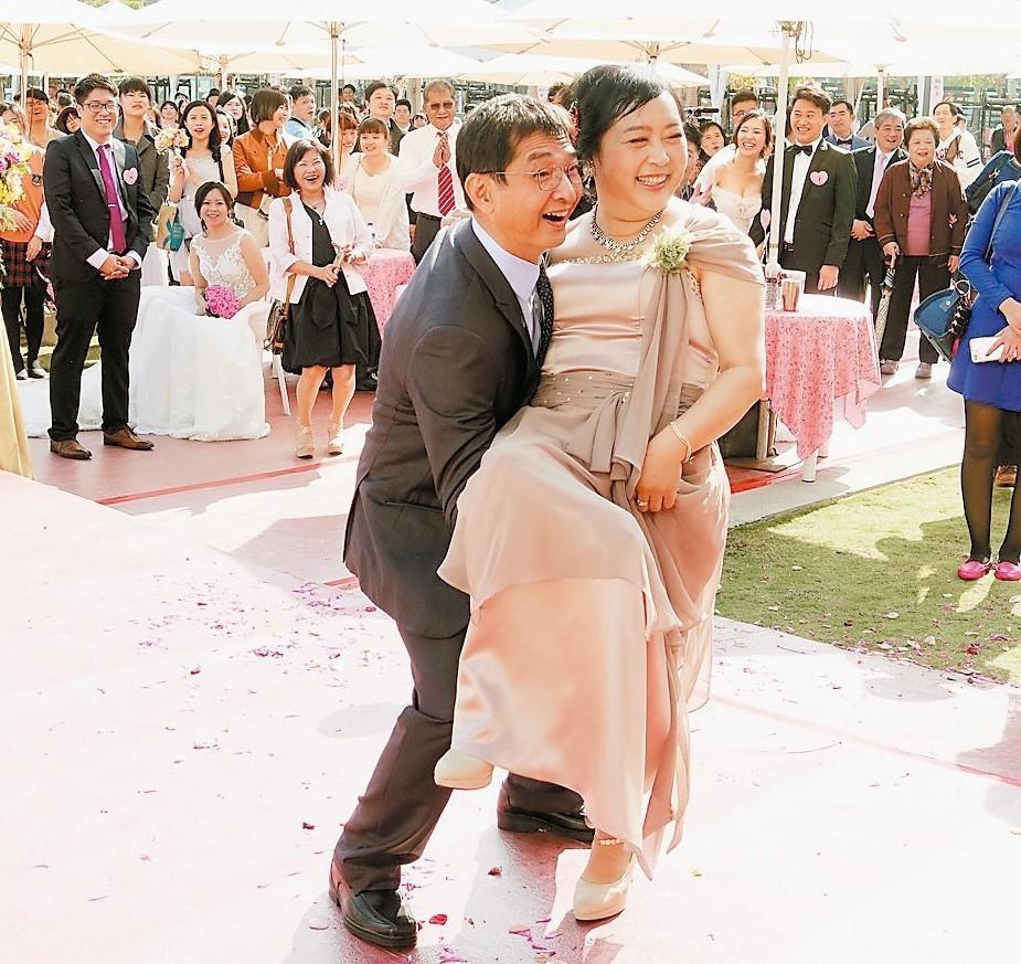 典禮中,安排新人父母示範「愛的家抱」,鼓勵新人有樣學樣,每天都要抱抱對方,感情才...