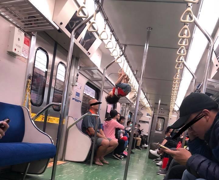 一名網友在「爆怨公社」貼出一名男童在區間車上,雙手握住吊環,整個人赤腳懸空倒吊車...