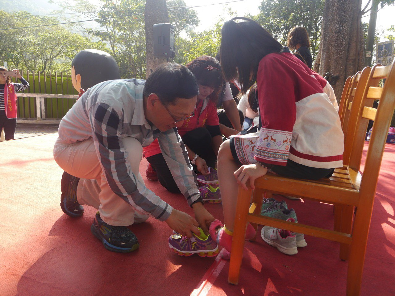 高雄市政府教育局長吳榕峯(左)替小朋友換穿新鞋。記者徐白櫻/攝影
