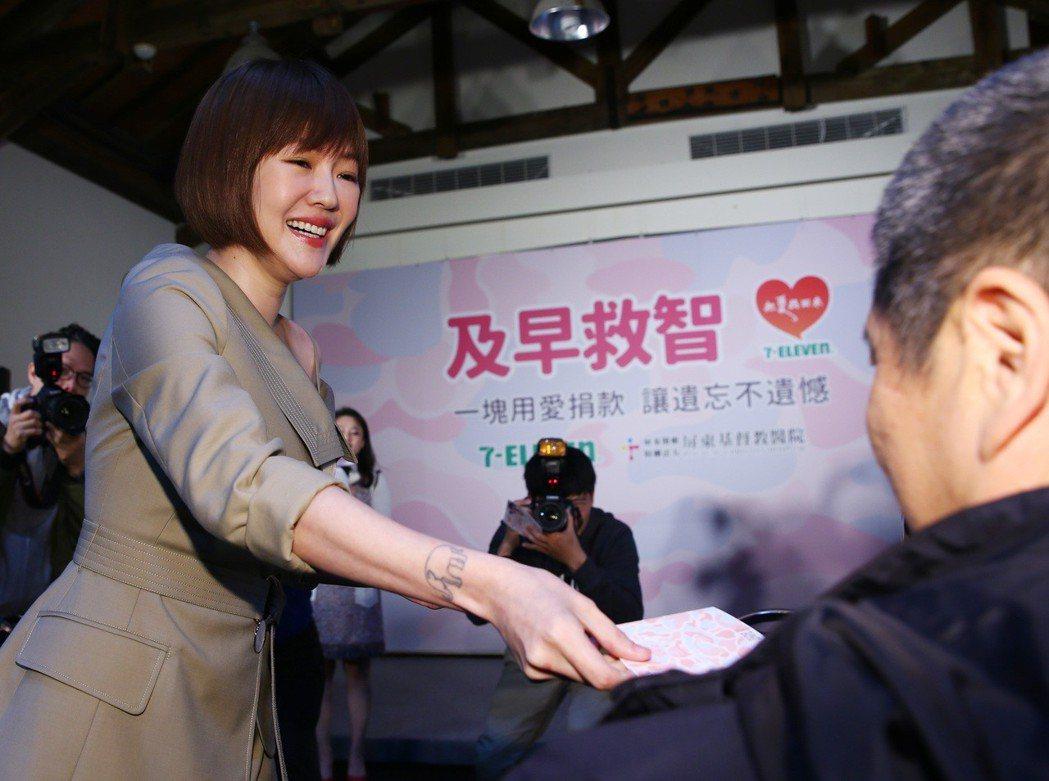 小S徐熙娣(左)為關懷失智症公益活動擔任募款愛心大使,在記者會上發送零錢收集袋給...