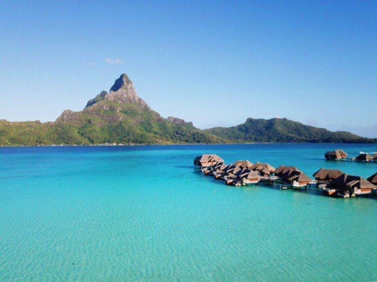 在層次深淺不同的瀉湖上,一排排的水上屋,搭配主島上的奧特瑪努山,可算得上是終極夢...