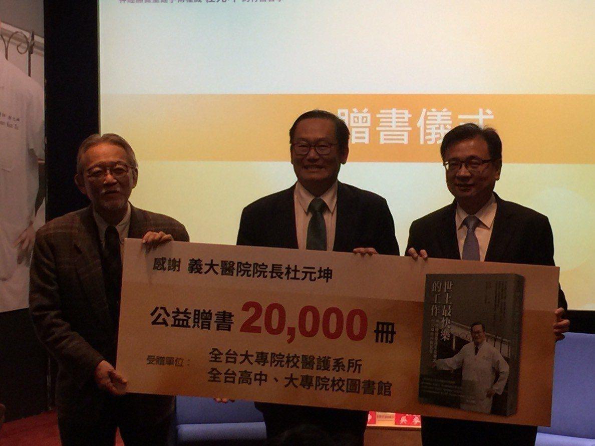 義大醫院院長杜元坤(中)昨捐贈2萬本新書「世上最快樂工作」給母校台北醫學大學。記...