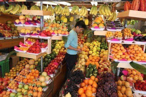 在秘魯首都利馬,小販挑出賣相好的水果。(路透)