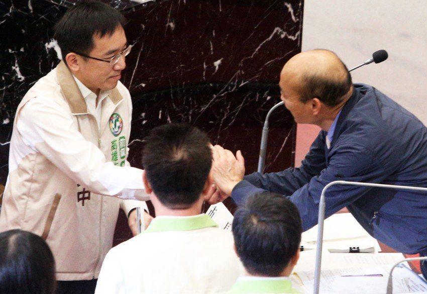 高雄市長韓國瑜(右)昨天首度進議會接受質詢,與民進黨議員陳致中(左)握手寒暄。記...