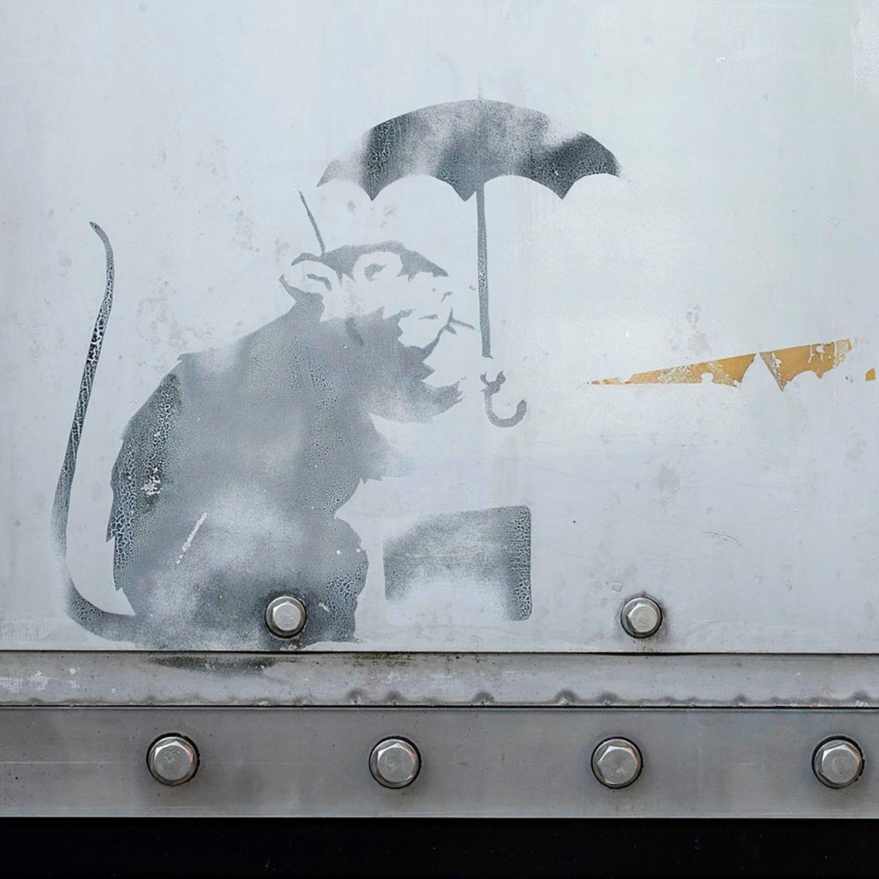 東京都一處防潮門有人塗鴉小老鼠撐傘圖,被傳可能是英國知名塗鴉藝術家班克西(Ban...