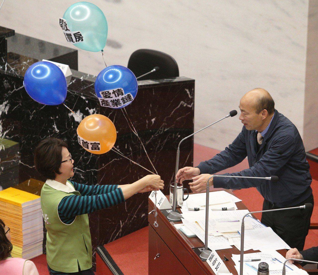 高雄市長韓國瑜(右)今天上午首度進議會接受質詢,民進黨議員林宛蓉(左)送上政見氣...