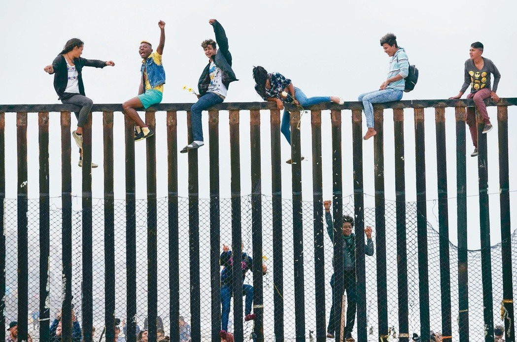 中美洲移民翻越美墨邊境圍籬硬闖美國。(法新社)