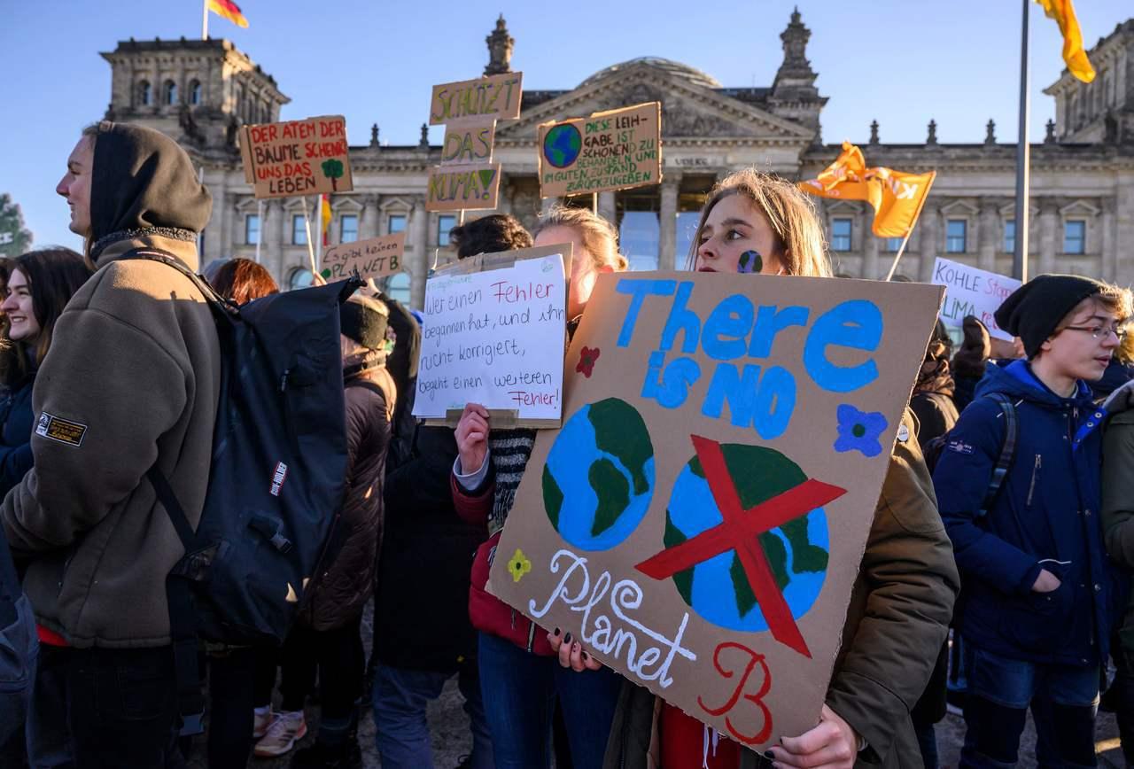 許多學生舉著抗議標語,呼籲政府正視氣候變遷。法新社