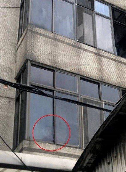 印尼籍25歲女移工阿娣在窗邊向外求援。圖/新北勞工局提供