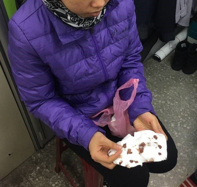 印尼籍25歲女移工阿娣拿著沾滿鮮血的衛生紙向外界求援。圖/新北勞工局提供