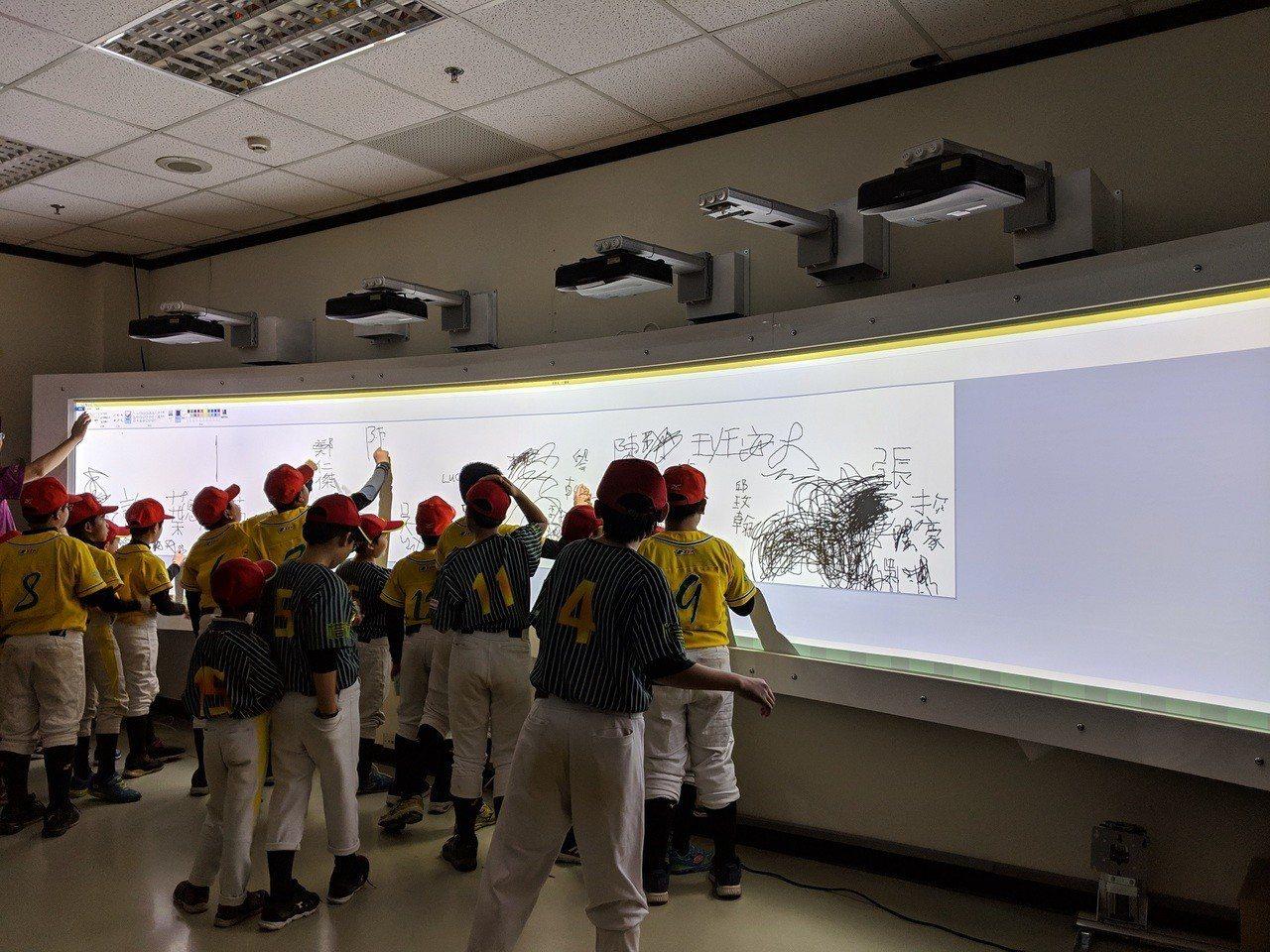 嘉義縣秀林國小棒球隊多位球員,同時於沉浸式觸控顯示系統上畫畫。圖/中光電提供