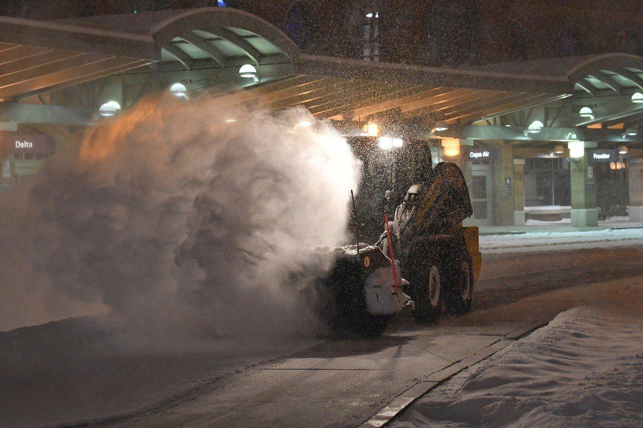 大雪紛茫,紐約州奧爾巴尼國際機場員工20日忙著剷雪。(美聯社)