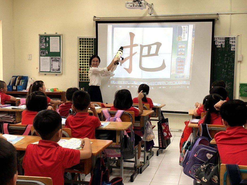 文藻外大實習生於胡臺校國語課堂書空練習演示,老師帶領同學以手指向空中書寫,學習國...