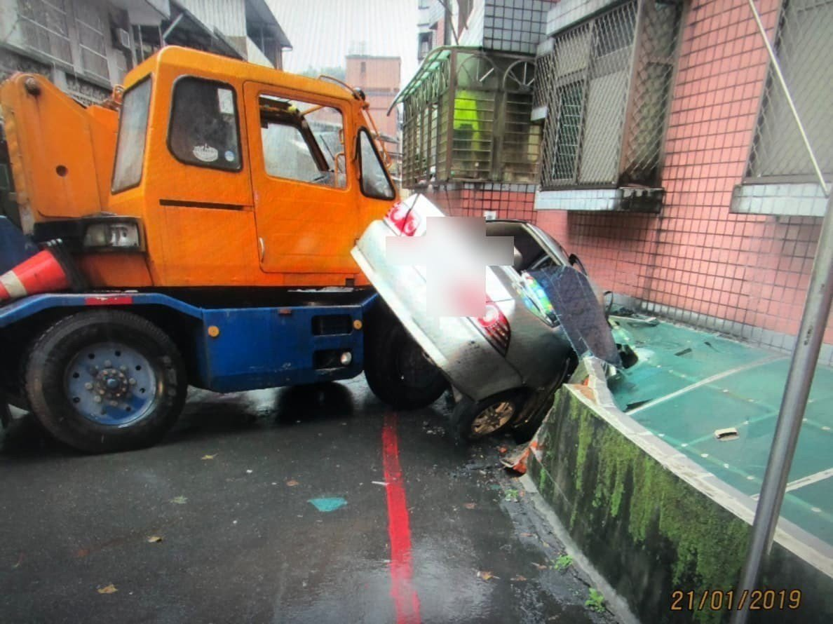 基隆市東信路今早11時許傳出一輛吊車疑似煞車失靈,狠狠撞上停放在路邊的銀色轎車,...