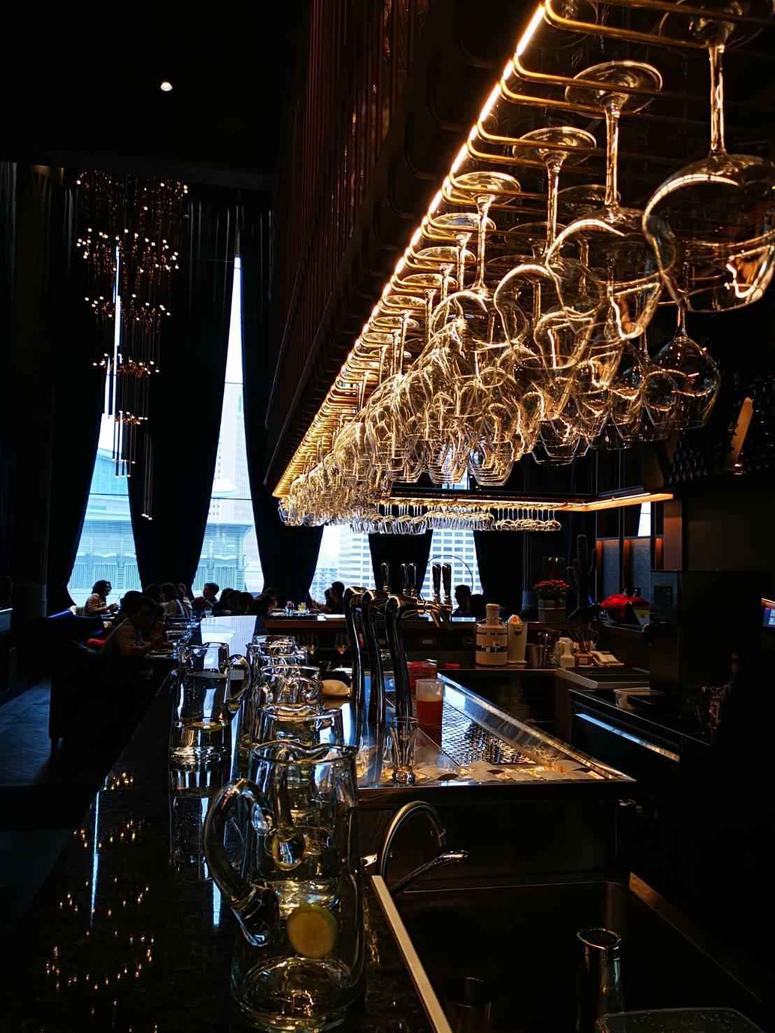 UMAMI的吧台設計,高腳杯倒吊並搭配金黃色燈光,營造時尚奢華感。記者韓化宇/攝...