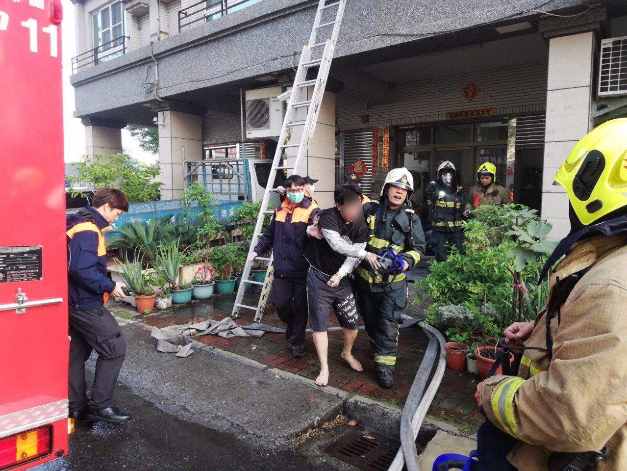 鳳祥分隊隊員蕭志明(中間右)找到受困三樓的洪姓男子(中間左),隨即將自己空氣面罩...