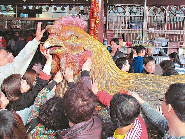 紫南宮的金雞很靈驗,信眾爭相摸金雞、求平安。 報系資料照