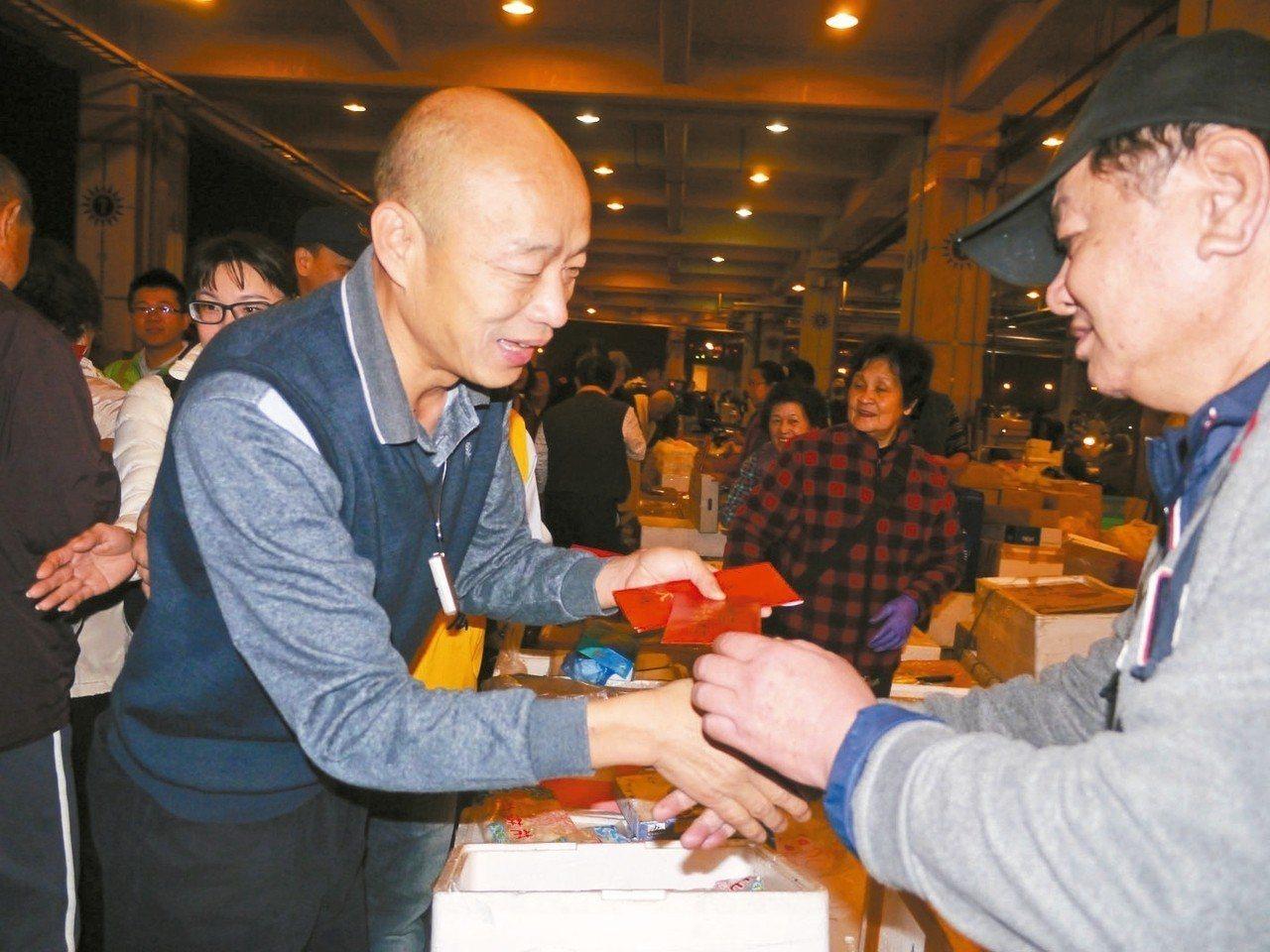 高雄市長韓國瑜(左)初次視察魚市場,發送紅包拜早年。 記者徐白櫻/攝影