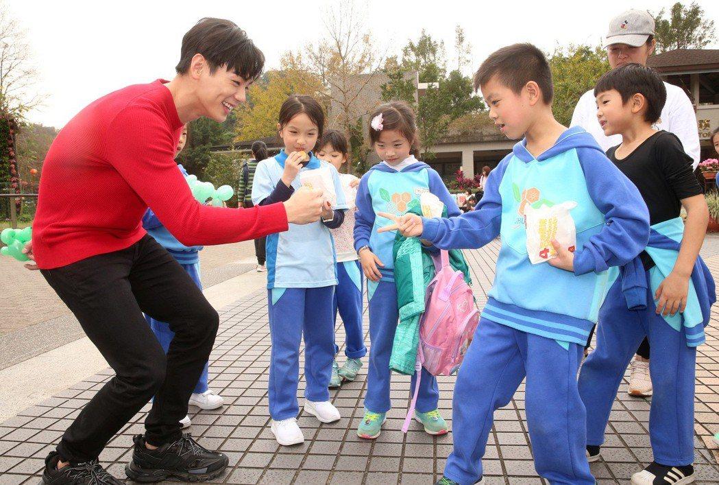 禾浩辰(布魯斯)過年遊動物園看豬,也跟現場小朋友開心玩猜拳遊戲,並送氣球。記者胡...