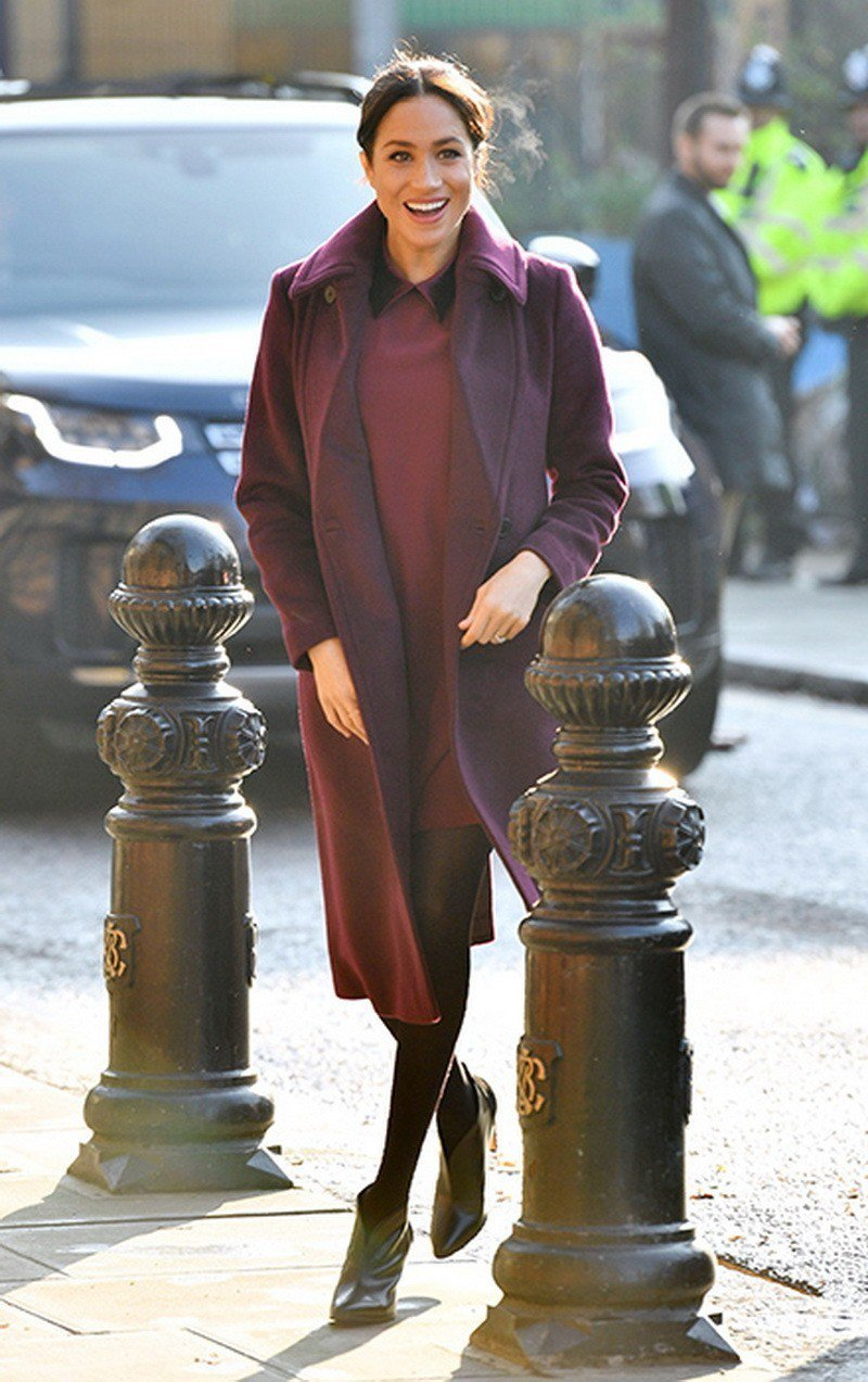 「最美孕婦」梅根近日以Club Monaco酒紅色縐綢洋裝搭配同色長版外套。圖/...