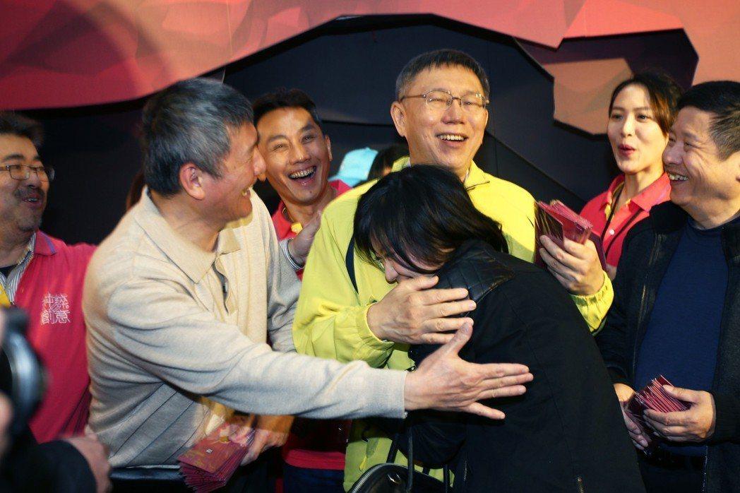 台北市長柯文哲23日下午到迪化商圈,民眾排隊領取發財金,一位女柯粉興奮的緊緊抱住...