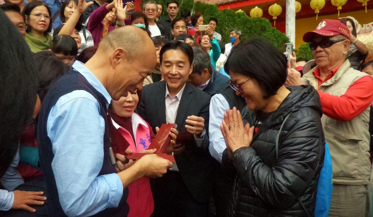 高雄市長韓國瑜(左)今天在高雄玉皇宮發紅包,領紅包民眾喜孜孜。記者林保光/攝影
