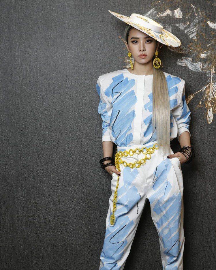 蔡依林身穿MOSCHINO春夏白底藍色塗鴉褲裝,搭配同品牌大耳環和腰鍊和印有金鍊...