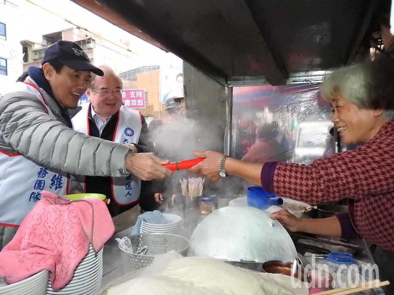 前總統馬英九(左一)今天陪鄭世維到三重大同南路市場掃街,不少民眾爭相索取春聯、合...