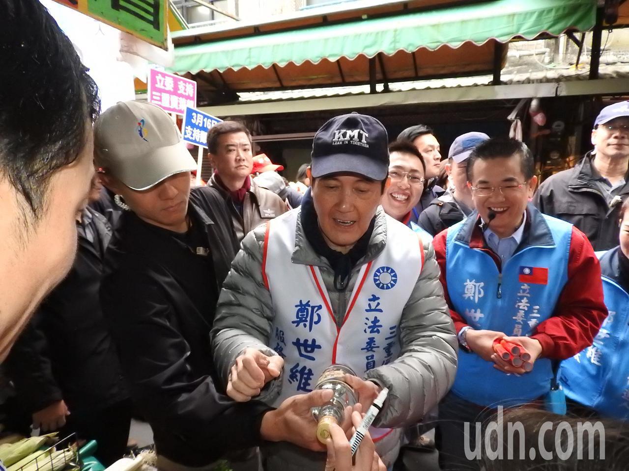 前總統馬英九(右二)今天陪鄭世維(右一)到三重大同南路市場掃街,不少民眾爭相索取...