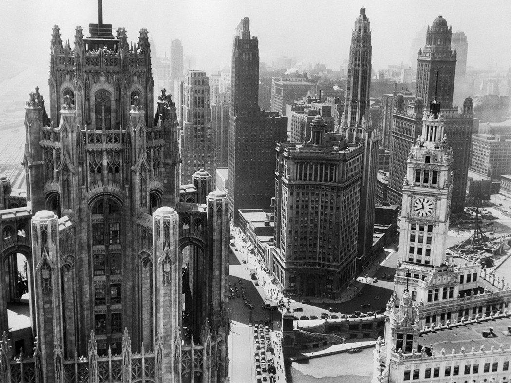 「讓土地吐出錢來。」電梯、鋼鐵結構、電話,使得土地得以無限向上「複製」。芝加哥因...