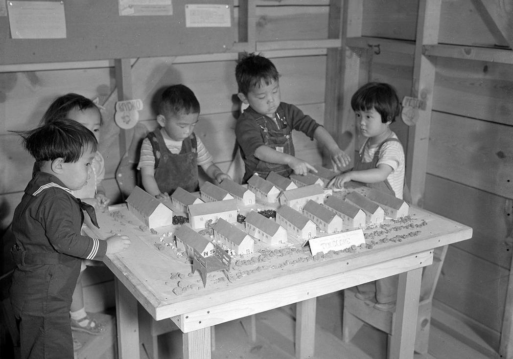 在拘留營當中,小孩正在玩建築模型積木。不過這個建築模型,其實也就是他們所生活的拘...