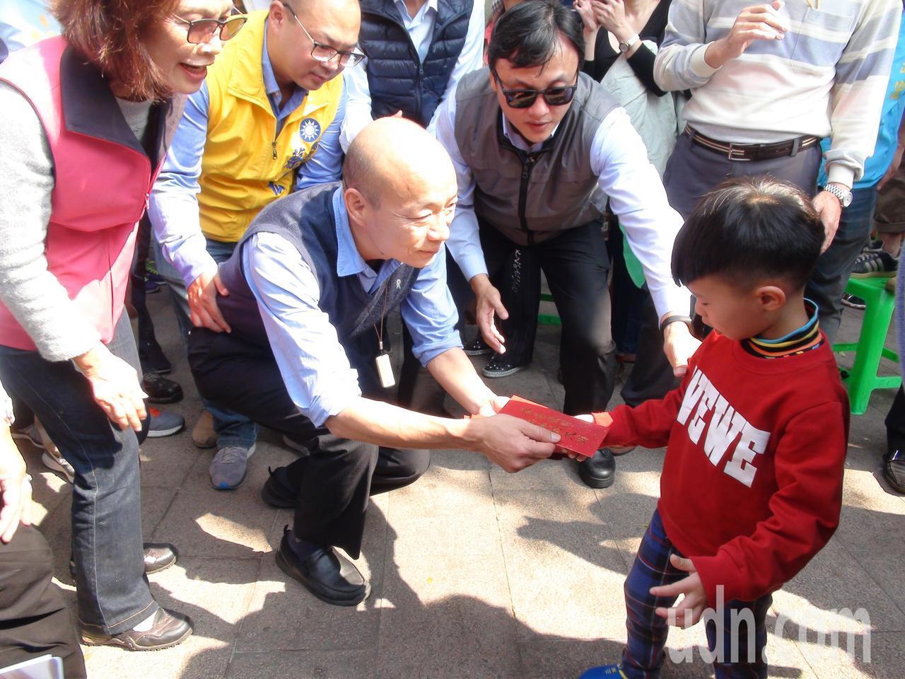 高雄市長韓國瑜發紅包,看到小孩,都會蹲下來發給小朋友。記者謝梅芬/攝影