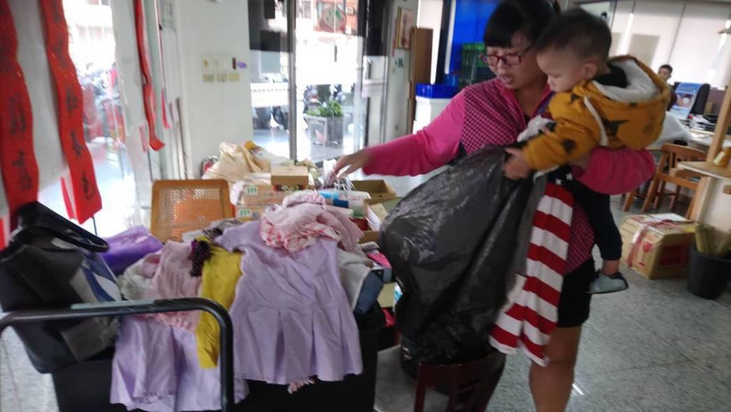 現場單親媽媽拿到跨海回台的愛心衣物,喜出望外如獲珍寶,正因年終將近,她沒錢買衣...