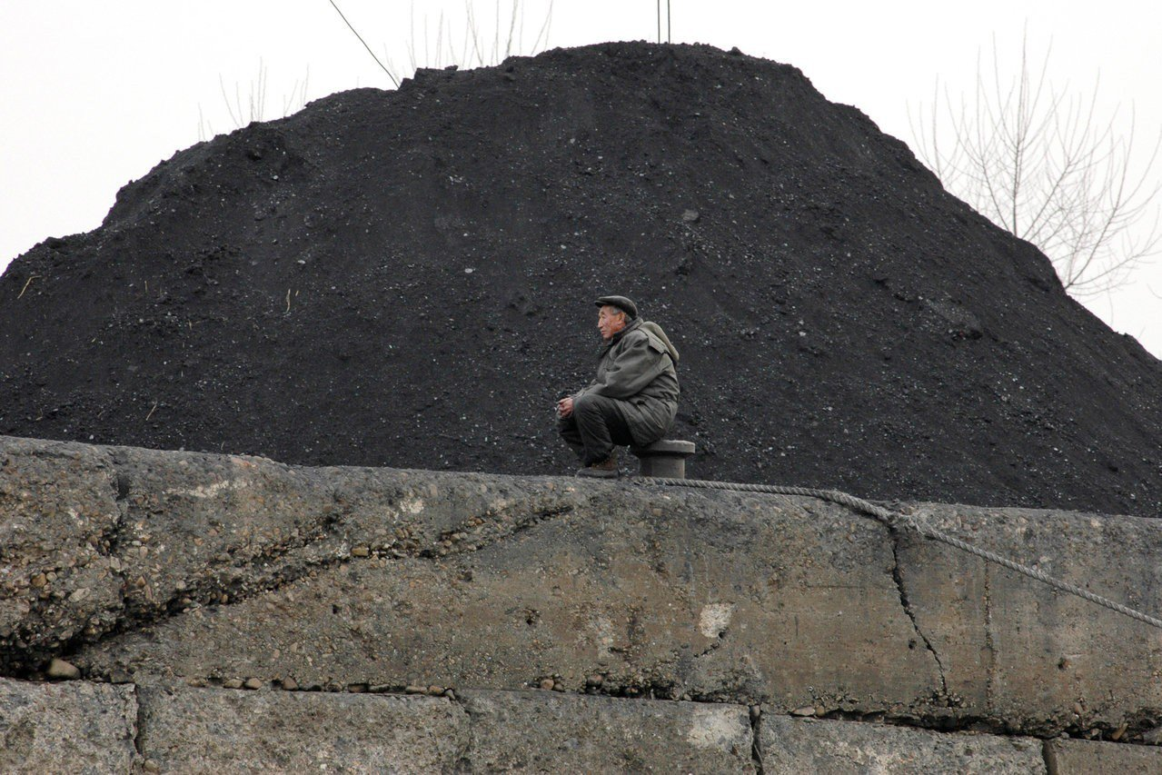 一名北韓男子坐在堆成小山的煤炭前。路透