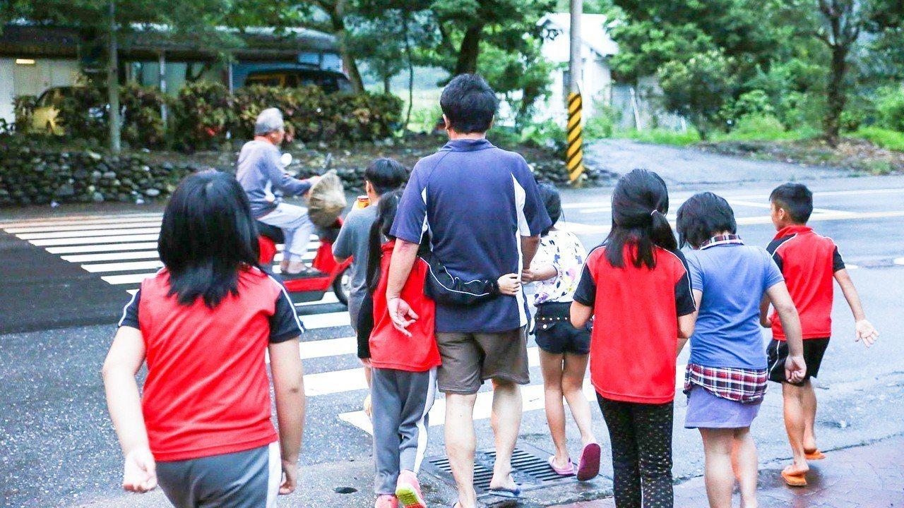 謝明賢生前與孩子過馬路背影。圖/翻攝謝明賢臉書