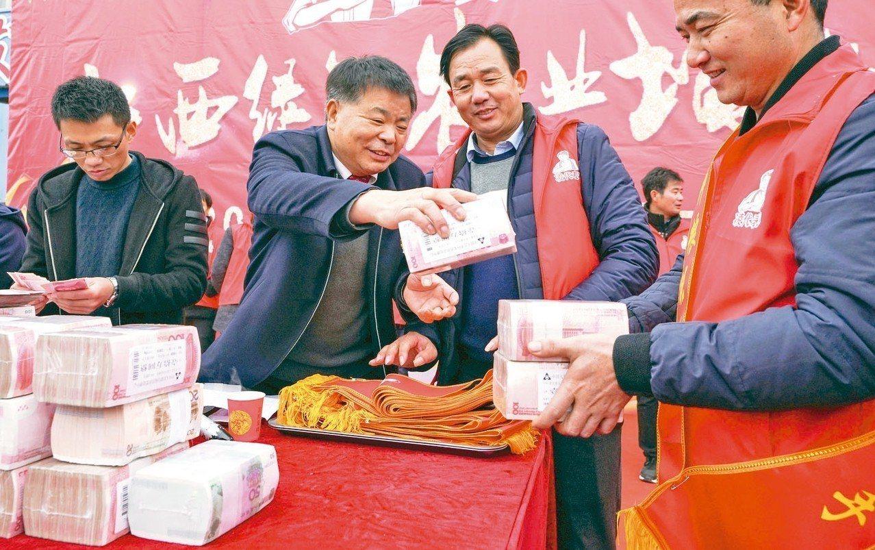 北京上班族年終獎金平均人民幣8,994元。圖為某陸企發放年終獎金。 (中新社)