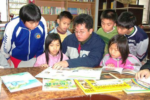 謝明賢(中)把閒置的春日部落聚會所變成兒童經常出入的圖書館,圖攝於2006年。圖...