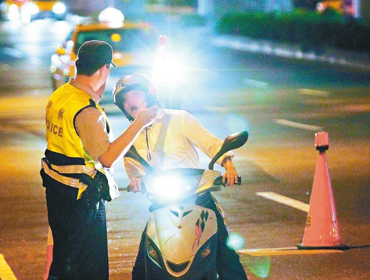 根據數據顯示,酒駕肇事件數及死亡人數以機車為大宗。圖為警方攔查機車騎士執行酒測勤...