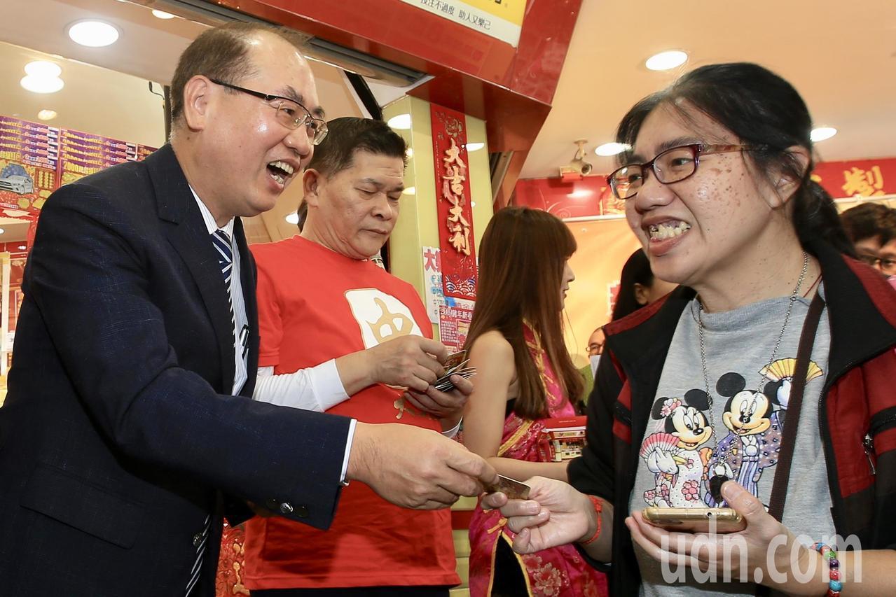 台彩上午舉行投注站造勢活動,台灣彩券公司總經理蔡國基(左)到現場和民眾拜早年,與...